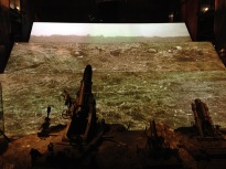 A three-panel video rotates showing the state of the battlefield.