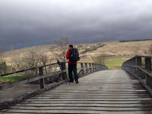 Jeff standing on the bridge toward the working farm.