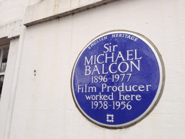 A plaque mounted on the outside of the white lodge of Ealing Studios.