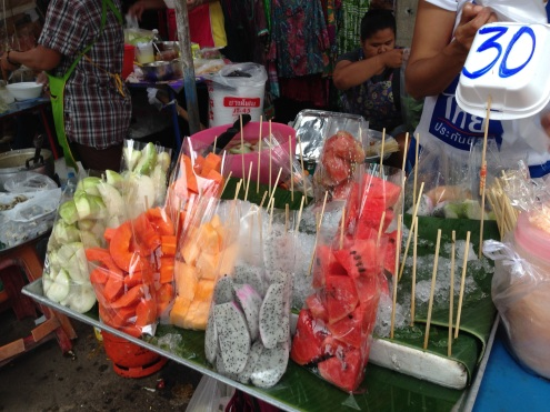 Dragonfruit and other fresh fruits for sale in bags.