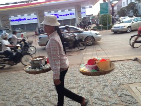 A woman carrying supplies toward Pub Street.