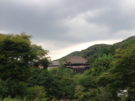 From the pagoda, the Kiyomizu-dera Temple surrounded by mountains and trees.