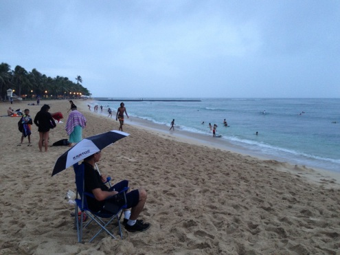 Despite the rain, this man stayed in place on the Waikiki Beach.